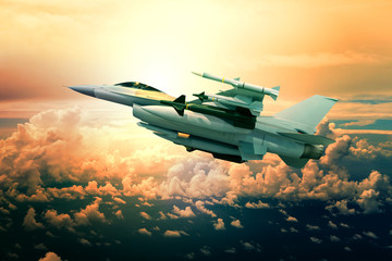 military jet plane with missile weapon flying against sunset sky
