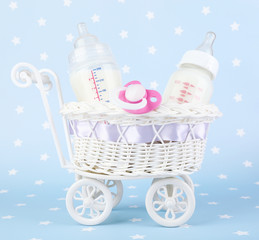Basket with baby milk bottle and pacifier on blue background