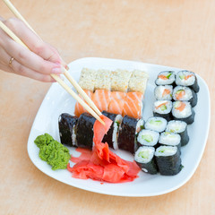 hand take ginger with chopsticks sushi plates