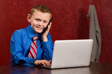 Young working boy with tie, phone and computer