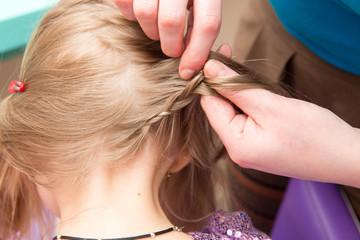 Hairdresser makes hairstyle child