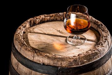 Glass of cognac on old oak barrel