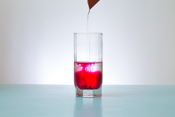 pours into glass red powder
