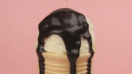 Chocolate sauce being poured over an ice cream cone