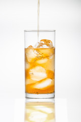 Iced Tea pouring into a glass of ice
