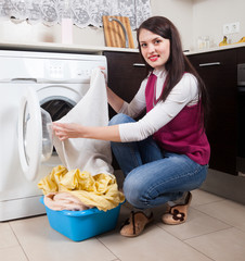 Smiling brunette woman doing laundry