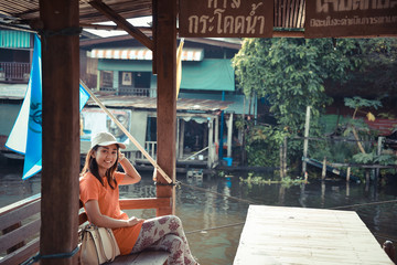 Cute Asian Thai girl is relaxing in the pavilion near he riversi
