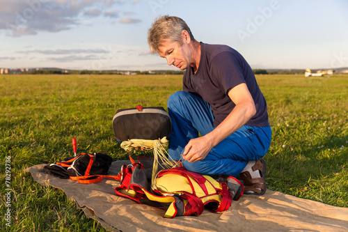 man puts  bag with parachute in   knapsack outdoor - 78292786
