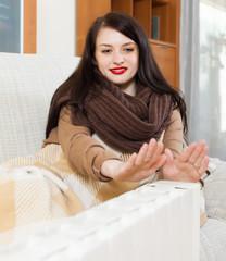 woman warming hands near calorifer