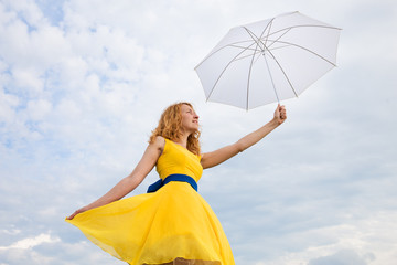 girl in yellow dress with white umbrella on background  sky
