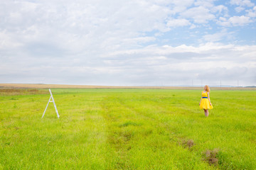 girl in yellow dress and stepladder in the field