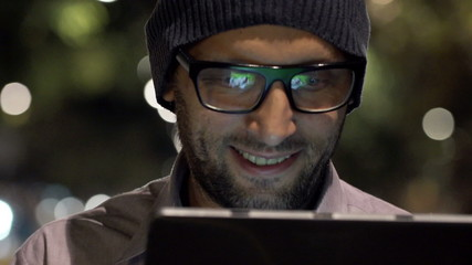 Young, handsome man with tablet computer in city at night