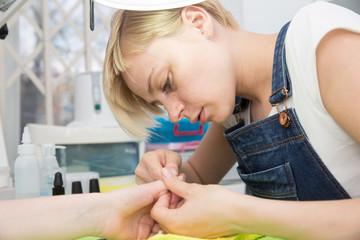 blonde doing manicure