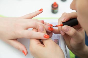 manicurists paints her nails painted orange