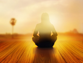 woman was meditating in sunrise and rays of light on landscape