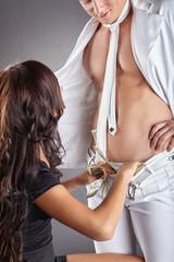 Woman puts money in pants of male stripper