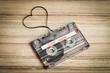 Audio cassette tape on wooden backgound. Film shaping heart