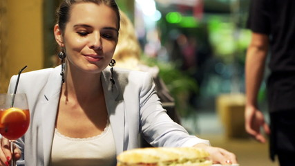 Young woman gets sandwich from waiter sitting in cafe at night