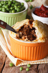Delicious meat pie in a pot and green pea. Vertical close-up