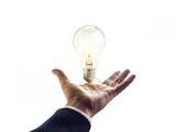 Fototapety Hands of a businessman reaching to towards light bulb
