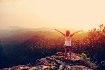 strong confident woman hiker open arms at on mountain peak rock