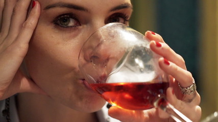 Close up of pensive woman drinking red wine in cafe at night