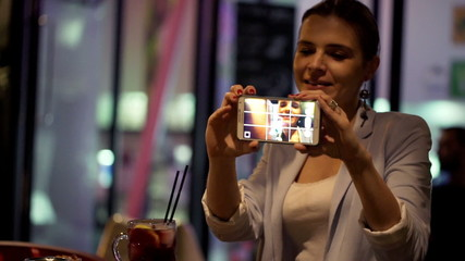 Young, pretty woman taking selfie photo with cellphone in cafe
