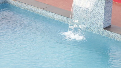 blue water slowly running into the swimming pool