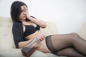 Sexy black hair woman in underwear holding glass of whiskey