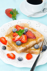 crispy toast with honey, fresh strawberries and blueberries