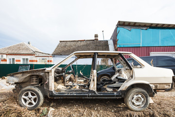 Disassembled car in village street