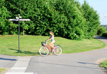 Woman bicyclist in green environment