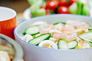 Delicious salad with shrimps and cucumber on a festive table