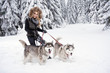 Happy young woman playing with siberian husky