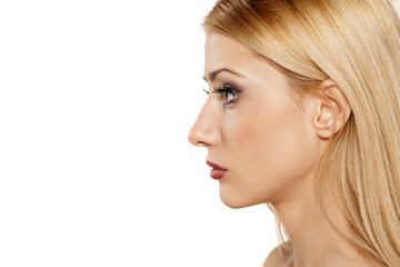 profile of serious young blonde on a white background