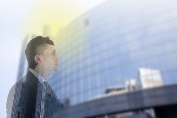 Double exposure of business man with office building