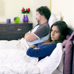 Unhappy couple in bed after fight not talking retro style