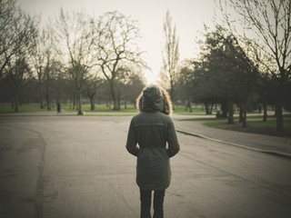 Person wearing warm coat standing in park at sunset
