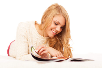 Young beautiful woman reading a magazine