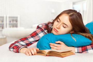 Young girl slepping with a book in bed