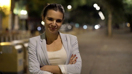 Portrait of happy, pretty woman in city at night