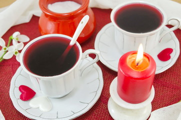 Two cups of tea and a burning candle