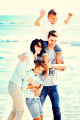Happy Small Family Having a Vacation at the Beach During Summer