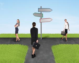 Three usinesswomen standing near sign