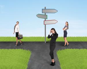 Three businesswomen and road sign
