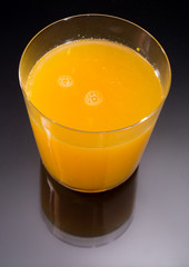 Top view of orange juice over black and glass reflection