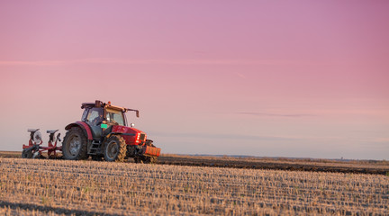 Farmer plowing field at sunset