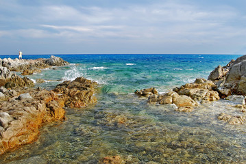 Sunny coastal landscape with rocks, agitated sea and cloudy sky