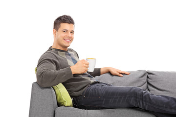 Relaxed young man drinking coffee seated on sofa