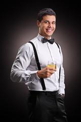 Vertical shot of a cheerful man drinking bourbon